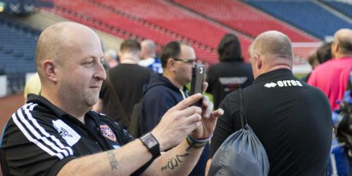 A group of male football fans standing in a football stadium; one fan is taking a photograph.